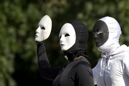aurillac: AURILLAC, FRANCE-AUGUST 25: two masked people play with their black and white masks as part of the Aurillac International Street Theater Festival, cie Bakhus 24,on august 25,2014, in Aurillac,France.