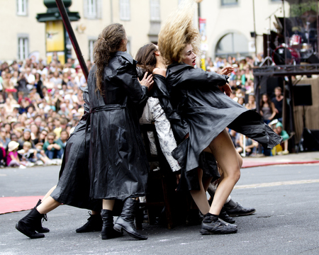 aurillac: AURILLAC, FRANCE-AUGUST 22: group of dancers wearing black raincoats as part of the Aurillac International Street Theater Festival, cie teatro del silencio ,on august 22, 2014, in Aurillac,France.