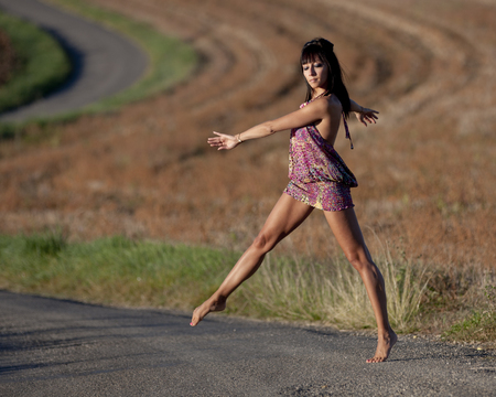 tiptoes: Young woman crossing a country road gracefully. She moves on tiptoes. She closed her eyes.