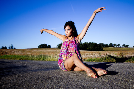 supple: Young supple dancer sits on a french country road. She Raises her arms gracefully.