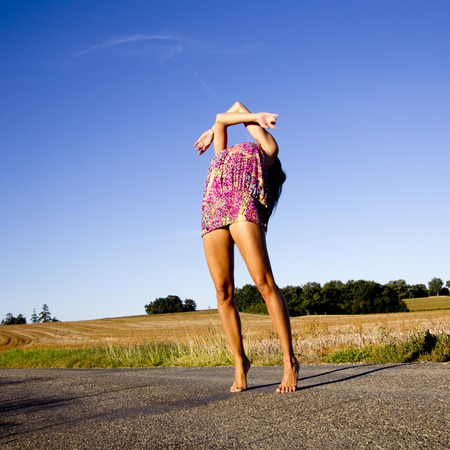 tiptoes: Who is supple young woman exercising herself barefoot on the asphalt of a french country road. She is on tiptoes, her head back and her arms raised. Stock Photo