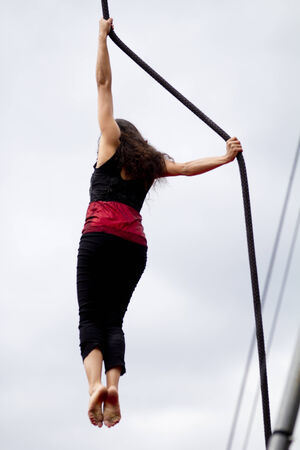 AURILLAC, FRANCE-AUGUST 22: a female acrobat is holding a rope as Strongly share of the Aurillac International Street Theater Festival, cie teatro del silencio there august 22, 2014 in Aurillac, France.