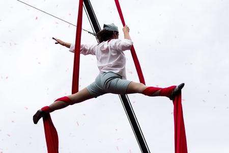 AURILLAC, FRANCE-AUGUST 22: an acrobat is hung with her legs wide open as share of the Aurillac International Street Theater Festival, cie teatro del silencio there august 22, 2014 in Aurillac, France.