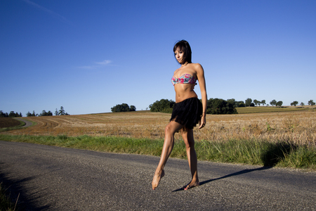 slowly: Young woman crossing a country road. She is barefoot. She wears a colored swimsuit top. In the background, stubble and blue sky.
