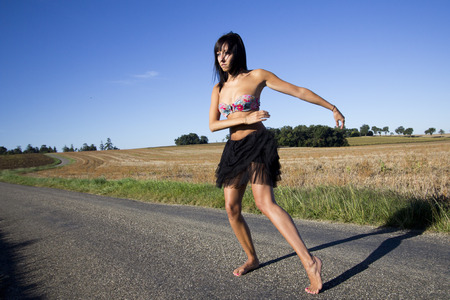 Young woman dancing on a country road. She is barefoot. She wears a colored swimsuit top.In the background, stubble and blue sky. photo