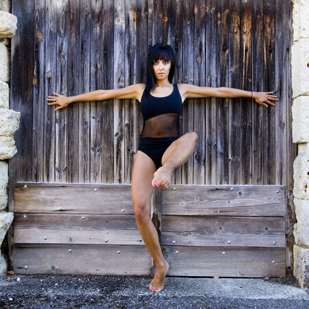 spreaded: Dancer wearing a black leotard, arms outstretched Against a wooden door. She is barefoot and she looks at the camera.