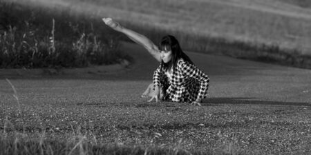 gracefully: Dancer on a country road. She wears a checked jacket. She sits on the asphalt and she lifts up one leg. She is barefoot. This image is a black and white photography. Stock Photo