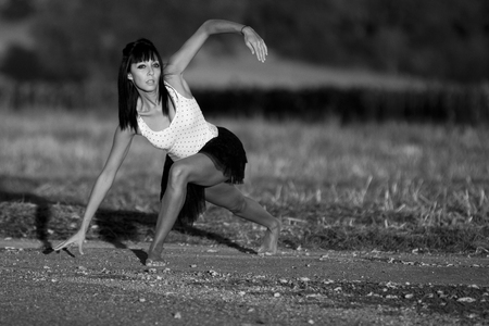 Young supple woman chooses to exercise on the edge of a country road under the first sunlights. She is barefoot. She wears a white top and a black skirt. This image is a black and white photography. photo