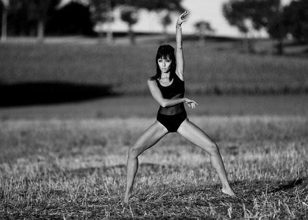 splayed: Gymnastic on the first sunlights. A woman moves in the middle of a field stubble. Legs splayed, bare feet, she raises one arm. She wears a black leotard. The image is a black and white photography. Stock Photo