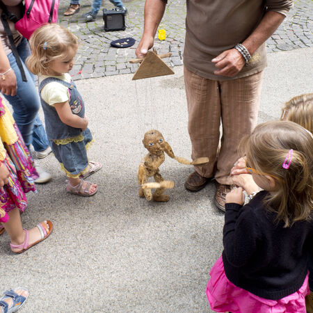 international puppet festival: AURILLAC, FRANCE, AUGUST 22: young children looking at a wooden hand puppet in the street as share of the Aurillac International Street Theater Festival, on august 22, 2014 in Aurillac, France.
