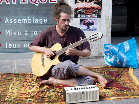 aurillac: AURILLAC, FRANCE, AUGUST 21: Barefoot and hairy musician playing the guitar in the street as share of the Aurillac International Street Theater Festival, on august 21, 2014 in Aurillac, France.