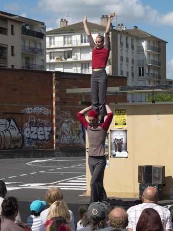 aurillac: AURILLAC, FRANCE, AUGUST 21: Female acrobat standing on the shoulders de son partner in the street as share of the Aurillac International Street Theater Festival, on august 21, 2014 in Aurillac, France.