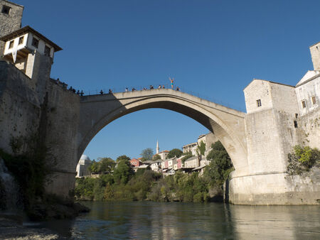 neretva: Man diving from the edge of the Old Bridge of Mostar, Bosnia. Arms outstretched, He is waiting for the money of the tourists to fall down Into the Neretva river.