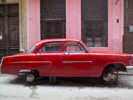 Vintage red car without wheels in a street of  Havana, beside a pink house.