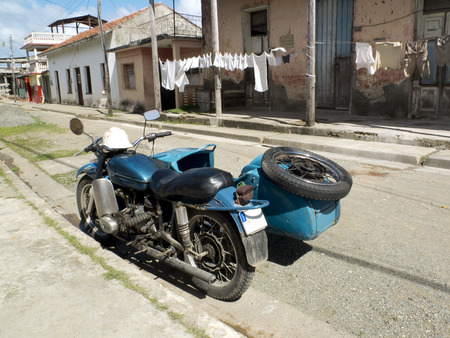 sidecar: Vintage blue sidecar in a street of Barracoa, Cuba. Some clothes are hung out to dry on the other side.