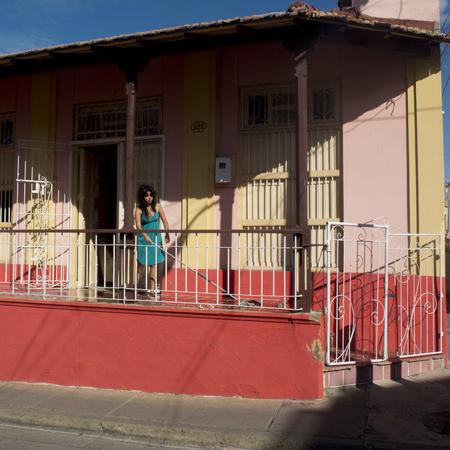 SANTIAGO DE CUBA, CUBA - NOVEMBER 29: a woman cleans the terrace with a floorcloth like She Does Every Day we november 29, 2014, in Santiago de Cuba, Cuba.