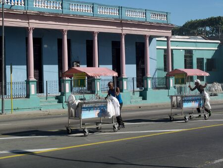 inhabitants: SANTIAGO DE CUBA, CUBA - NOVEMBER 29: In the middle of the road, two street vendors push carts to sell Their fresh drinks in the town, we november 29, 2014, in Santiago de Cuba, Cuba. Editorial