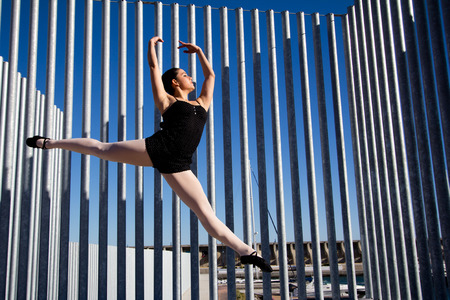salto de valla: Salto agraciado de una bailarina cl�sica en M�laga. Ella viste ropa oscura, y blackshoes medias blancas. Ella levanta sus brazos sobre su cabeza. En el fondo hay una valla hecha con tubos de metal de alta.