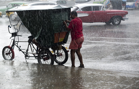rainfall: AVANA, CUBA - NOVEMBER 21: the driver of a rickshaw tries to close the protective cover de son vehicle under intense rainfall year in the city center, on november 21, 2014, in Havana, Cuba.