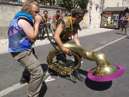 cantal: AURILLAC, FRANCE - AUGUST 19: a strange attitude to play the tuba in the street as part of the Aurillac International Street Theater Festival, on august 19, 2015, in Aurillac,France