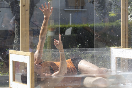 raises: AURILLAC, FRANCE - AUGUST 21: a dancer who is lying in the water in a transparent cube raises her arms, as part of the Aurillac International Street Festival,  on august 21,2015, in Aurillac,France. Editorial