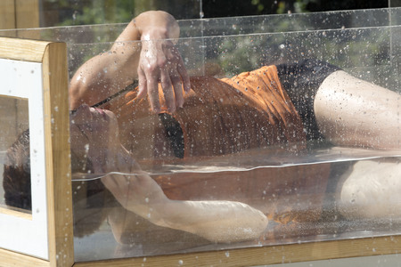 cantal: AURILLAC, FRANCE - AUGUST 21: Dancer lying in the water in a transparent cube, as part of the Aurillac International Street Theater Festival,  compagniekatchaa,on august 21,2015, in Aurillac,France.
