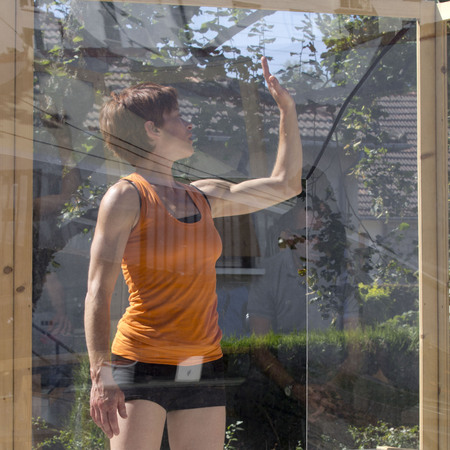 aurillac: AURILLAC, FRANCE - AUGUST 21: a woman raises her arm along a transparent wall, as part of the Aurillac International Street Theater Festival, compagniekatchaa, on august 21, 2015,in Aurillac,France.