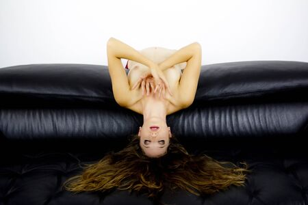 Attractive woman leaning against a black sofa. She puts her head back and she holds her hands against her bare chest.She has long hair. Stock Photo