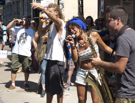 aurillac: AURILLAC, FRANCE - AUGUST 19: a man and a woman sing in the street with a saxophonist, as part of the Aurillac International Street Festival, Seed J Cie,on august 19, 2015, in Aurillac, France. Editorial
