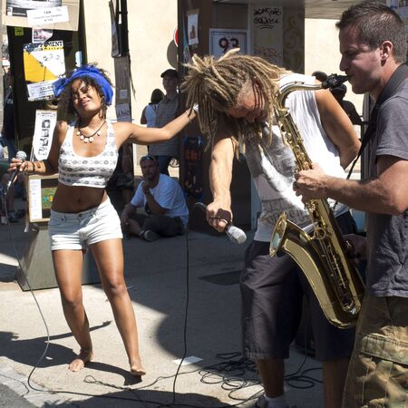 aurillac: AURILLAC, FRANCE - AUGUST 19: two singers play in the street with a saxophonist as part of the Aurillac International Street Festival,  Seed J Cie,on august 19, 2015, in Aurillac, France. Editorial