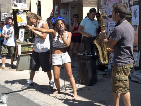 AURILLAC, FRANCE - AUGUST 19: a woman sing in the street  face to face with a saxophonist, as part of the Aurillac International Street Festival,  Seed J Cie, on august 19, 2015, in Aurillac, France.