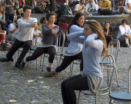 cantal: AURILLAC, FRANCE - AUGUST 19: dancers are moving on chairs in front of spectators in the street, as part of the Aurillac International Street Festival, on august 19, 2015, in Aurillac, France.