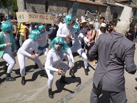 aurillac: AURILLAC, FRANCE - AUGUST 19: parade of street performers wearing green-blue wigs and white uniforms, as part of the Aurillac International Street Festival, on august 19, 2015, in Aurillac, France.