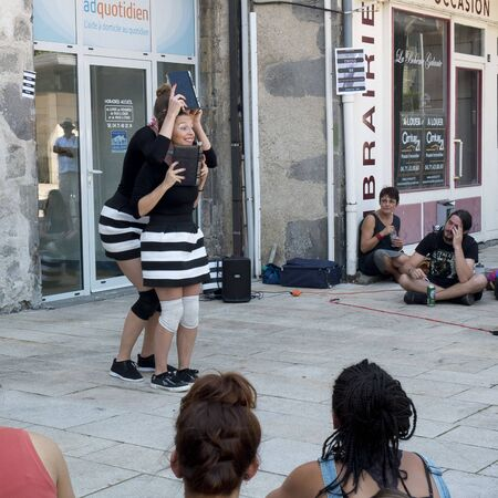 AURILLAC, FRANCE - AUGUST 19: two actresses, wearing skirts with black and white stripes, play in the street, as part of the Aurillac International Street Festival, on august 19, 2015, in Aurillac, France.