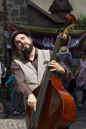 AURILLAC, FRANCE - AUGUST 19: a musician is playing double bass in the street, as part of the Aurillac International Street Festival, on august 19, 2015, in Aurillac, France.
