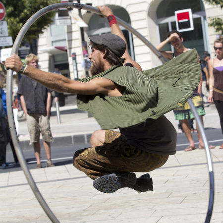 AURILLAC, FRANCE - AUGUST 19: a man uses a big hoop to move in the street , as part of the Aurillac International Street Festival, on august 19, 2015, in Aurillac, France. Editorial