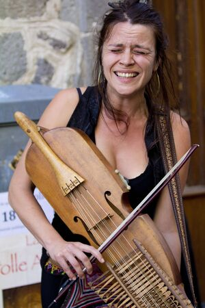 AURILLAC, FRANCE - AUGUST 20: Woman playing nyckelharpa in the street, as share of the Aurillac International Street Theater Festival, is august 20, 2015 in Aurillac, France. Editorial
