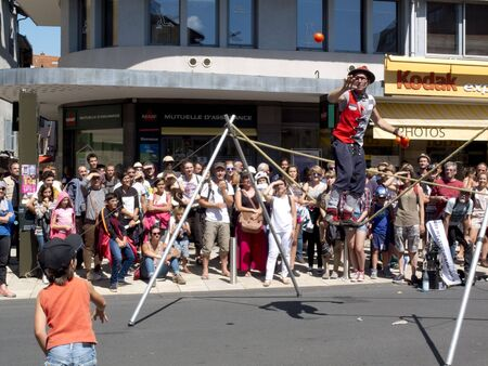aurillac: AURILLAC, FRANCE - AUGUST 19: a child is throwing a ball to a juggler balancing on a rope, as share of the Aurillac International Street Theater Festival, is august 19, 2015 in Aurillac, France.