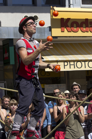cantal: AURILLAC, FRANCE - AUGUST 19: a juggler is playing in the street with red balls, as share of the Aurillac International Street Theater Festival, is august 19, 2015 in Aurillac, France. Editorial