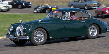 Nogaro, France - October 9, 2016: Old green Jaguar going fast on a motor-racing circuit during the Classic Festival.