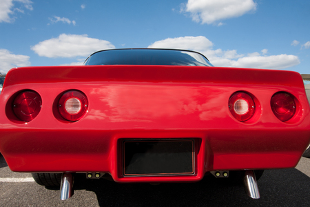 Rear view of a red car body. You can see aussi oven rear lights and two exhaust pipes. In the background, the sky is sunny and cloudy.