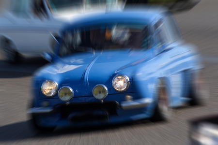 zooming: Zooming on a blue french because going fast. Vehicle headlights are on.