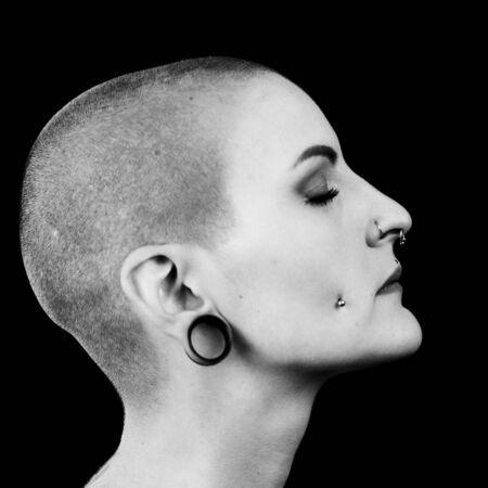 Portret in profiel van een mooie vrouw. Ze heeft haar hoofd kaalgeschoren en heeft gesloten ogen. Ze heeft piercings en oorbellen.