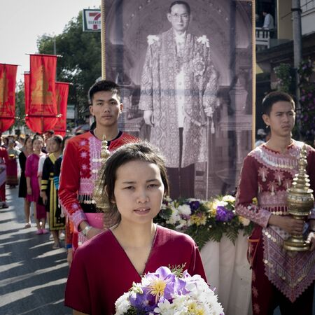 CHIANG MAI, THAILAND-FEBRUARY 4th 2017: Chiang Mai Flower Festival: procession of solemn young people carrying a very large portrait of King Bhumibol banner and other red banners. Thai people celebrate the very popular King death in 2016. Redactioneel