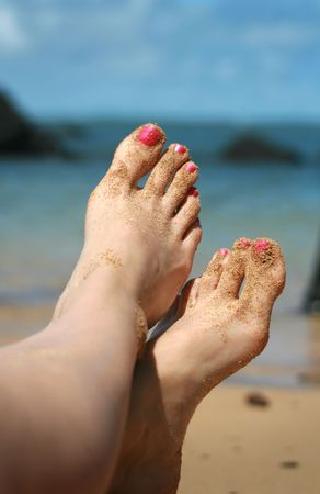 Newly manicured, sand covered toes relaxing on a tropical beach