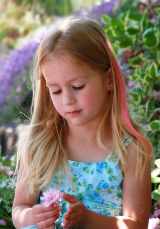 tenderly: Young girl tenderly holds a pink cherry blossom