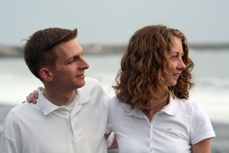 ponder: A young couple ponder their future at the beach. Stock Photo