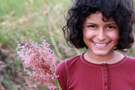 costa rican: Pretty young Hispanic girl with bouquet of pink wildflowers