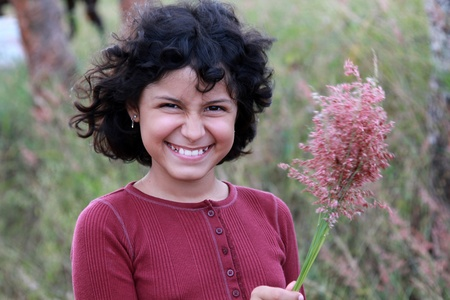 A young hispanic girl holding wildflowers in the breeze photo