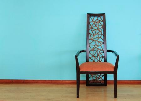 Modern wood chair against a blue wall photo